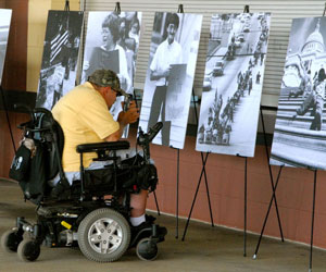 man in wheelchair looking at posters from the disability rights movement